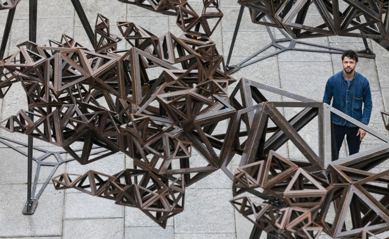 Conrad-Shawcross-RA-stands-in-front-of-The-Dappled-Light-of-the-Sun,-2015-©-Royal-Academy-of-Arts,-Benedict-Johnson-1.jpg